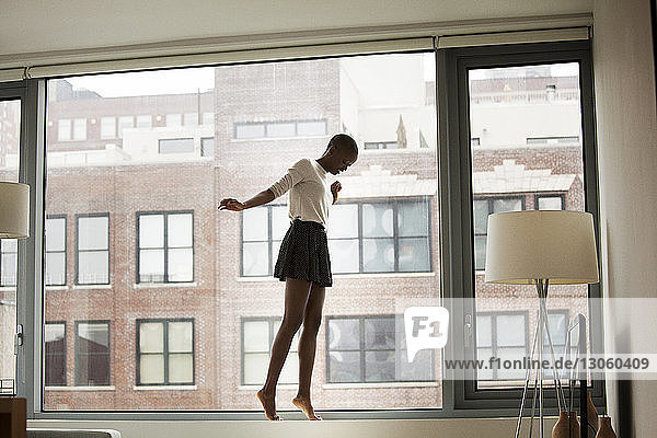 Woman tiptoeing on window sill at home