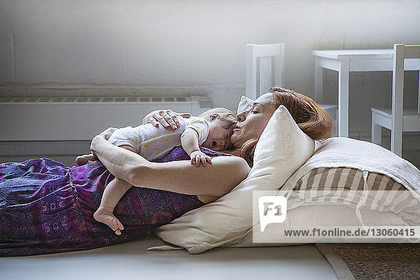 Mother embracing baby girl while lying on floor at home