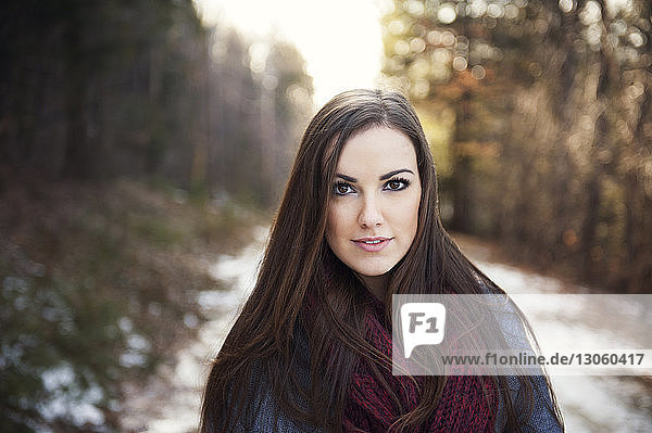 Portrait of confident woman standing in forest during winter