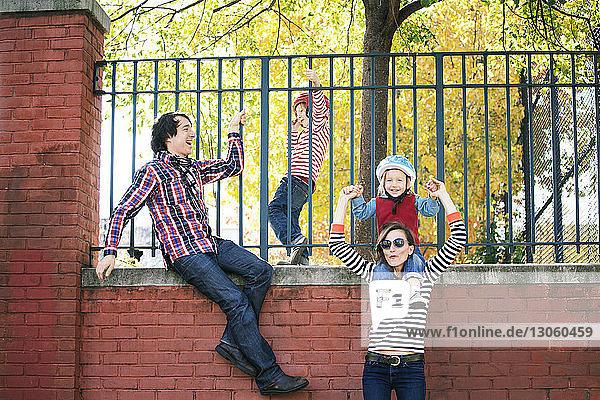 Familie genießt durch Zaun an Stützmauer