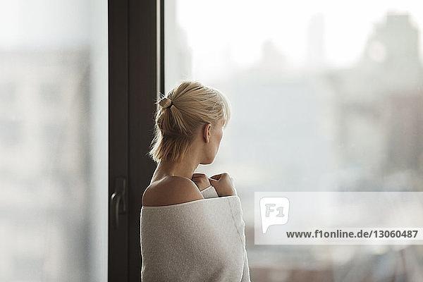 Seitenansicht einer in ein Handtuch gehüllten Frau  die zu Hause am Fenster steht