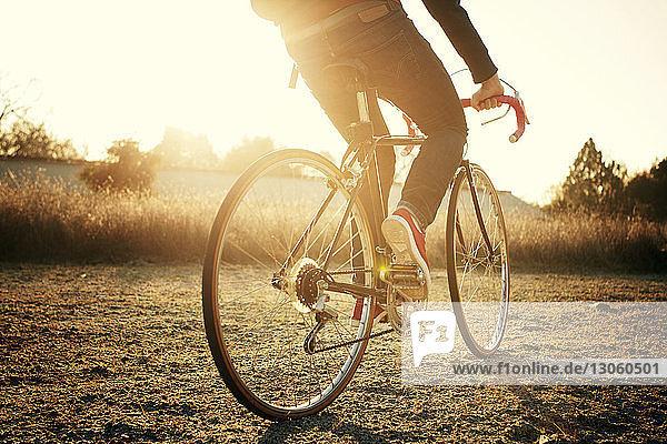 Niedriger Abschnitt eines Mannes  der bei Sonnenuntergang auf der Straße Fahrrad fährt Niedriger Abschnitt eines Mannes, der bei Sonnenuntergang auf der Straße Fahrrad fährt