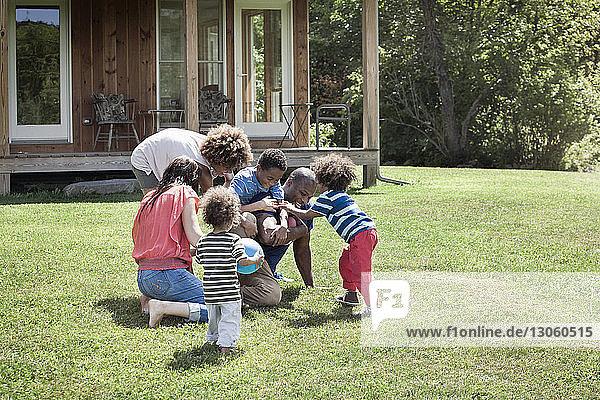 Glückliche Eltern spielen mit Kindern im Garten Fussball