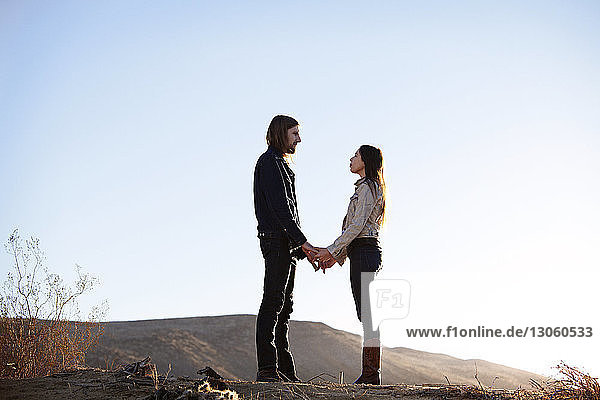 Couple holding hands while standing face to face on field against clear sky