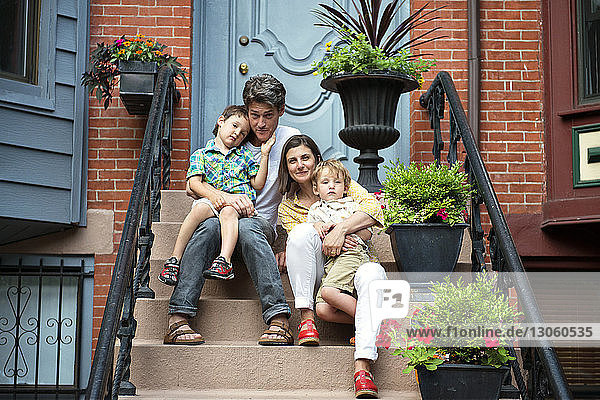 Portrait of smiling family sitting on steps outside house