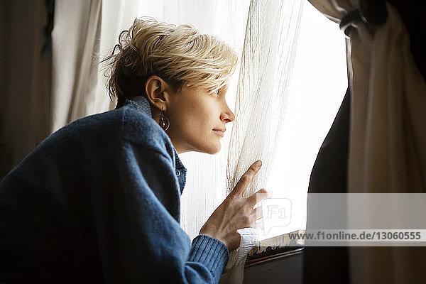 Frau hält Vorhang  während sie durch das Fenster wegsieht
