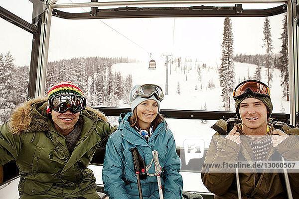 Porträt von glücklichen Skifahrern  die in der Luftseilbahn sitzen