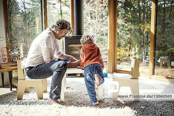 Vater bringt Sohn das Schreiben bei  während er zu Hause auf einem Stuhl sitzt