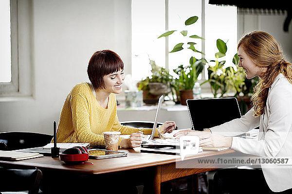 Weibliche Fotoredakteurinnen diskutieren am Schreibtisch im Kreativbüro