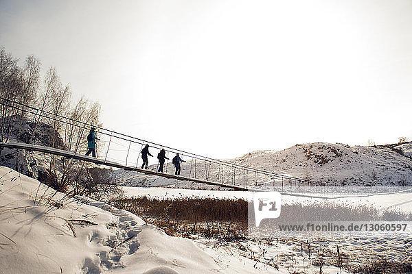 Freunde gehen im Winter bei klarem Himmel auf einer Fußgängerbrücke