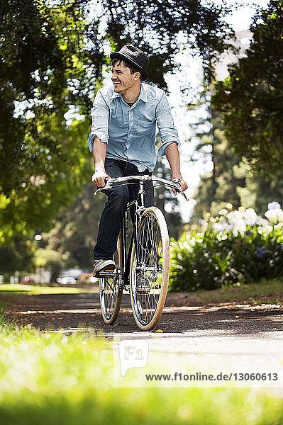Glücklicher Mann fährt Fahrrad im Park