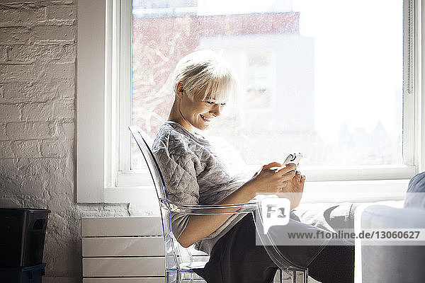 Side view of happy woman using smart phone at home