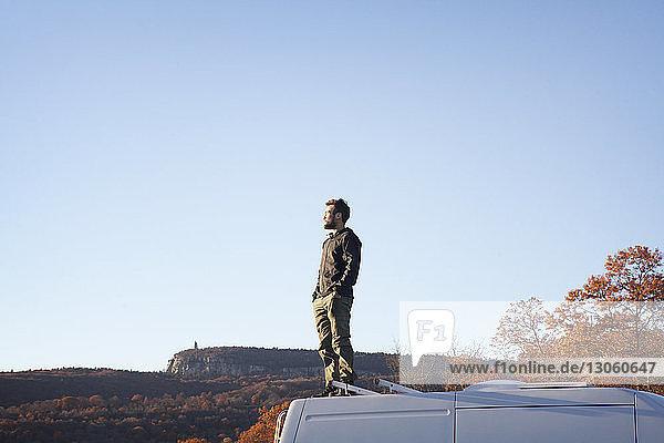 Mann mit Händen in der Tasche steht auf Wohnmobil vor klarem Himmel