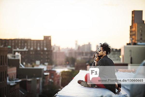 Paar schaut weg  während es bei Sonnenuntergang auf einer Stützmauer sitzt