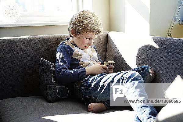 Boy using mobile phone while sitting on sofa at home