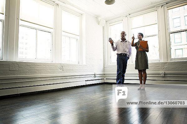 Geschäftsleute diskutieren  während sie im Amt gegen das Fenster stehen
