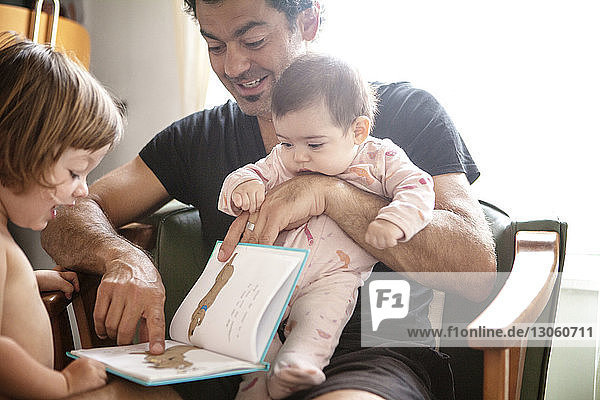 Father reading book to daughters while sitting on chair at home