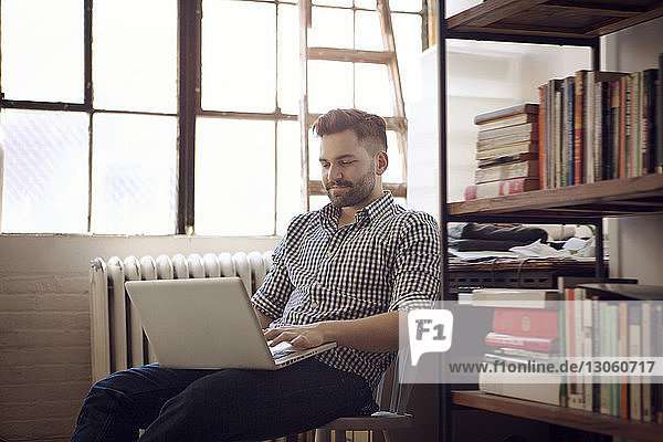 Man using laptop computer while sitting on chair at home