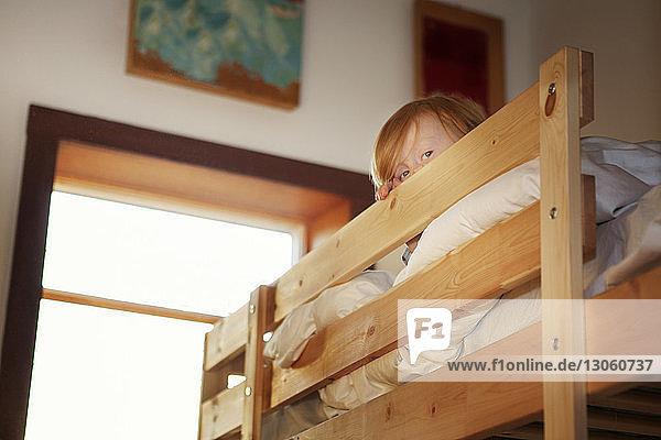 Porträt eines Jungen in der Koje zu Hause