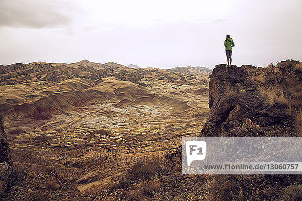 Frau steht auf Klippe gegen Berge
