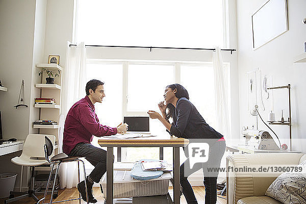 Businessman having discussion with female colleague at table in creative office
