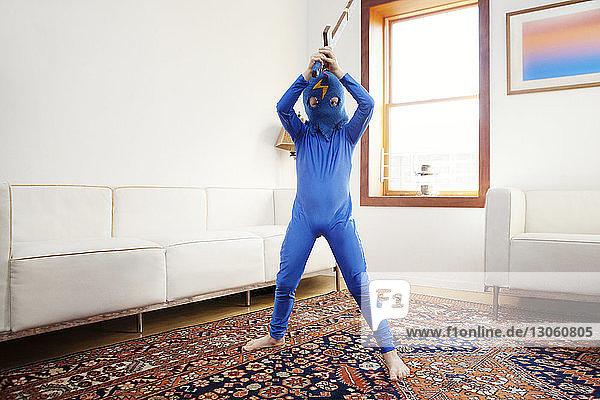 Junge im Superhelden-Kostüm hält Schwert  während er zu Hause steht