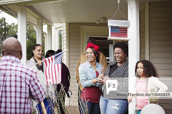 Glückliche Frauen schauen einen Mann mit amerikanischer Flagge vor dem Haus an