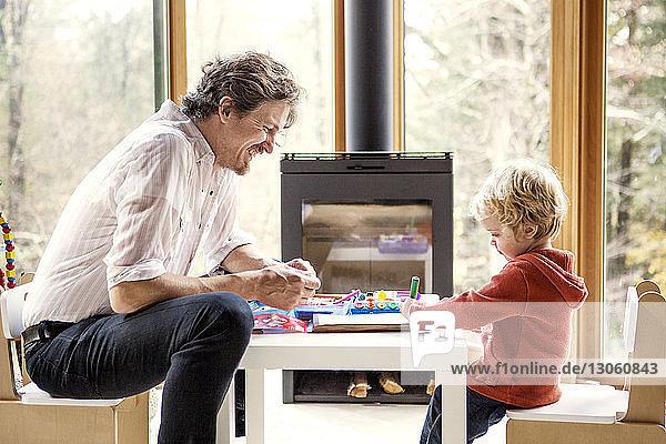 Seitenansicht eines Vaters  der seinem Sohn das Schreiben beibringt  während er zu Hause auf einem Stuhl sitzt