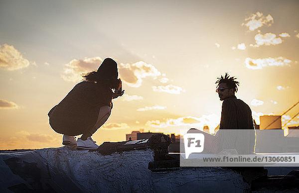 Rückansicht einer Frau  die den Sonnenuntergang durch ein Mobiltelefon fotografiert  während sie auf einer Stützmauer kauert