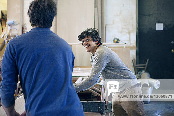 Happy carpenter talking to colleague while working in workshop