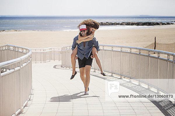 Glücklicher Mann nimmt Frau huckepack  während er am Strand auf der Strandpromenade spazieren geht