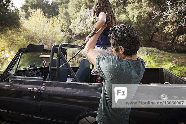 Vater assistiert Tochter beim Sitzen am Geländewagen