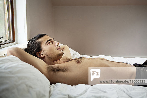 Shirtless man looking away while lying on bed at home