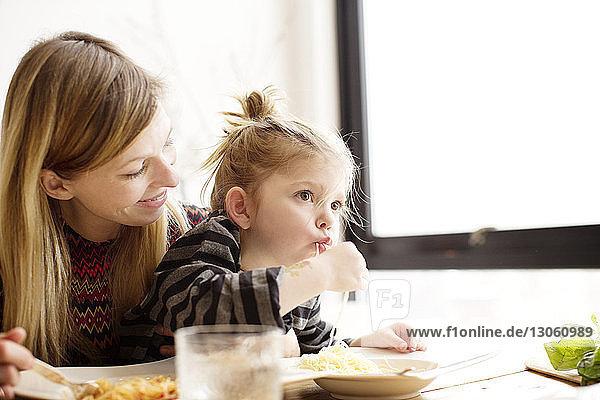 Mutter sieht Tochter bei Tisch beim Nudelnessen an