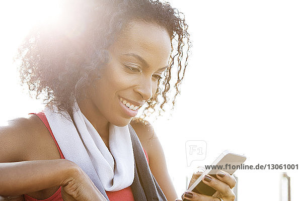 Happy woman using phone during sunny day