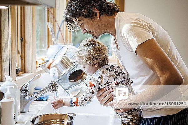Vater trägt Sohn beim Händewaschen an der Küchenspüle