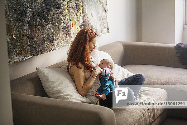 Mother feeding baby girl while sitting on sofa at home