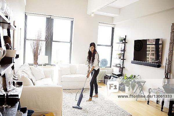 Frau saugt zu Hause im Wohnzimmer Staub