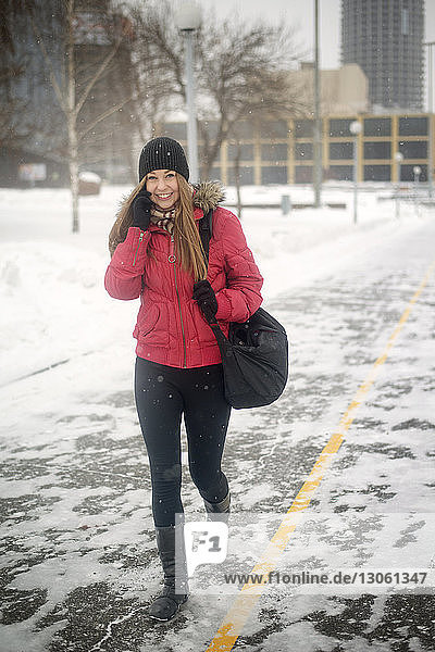 Portrait of happy young woman talking on mobile phone while walking on road during winter