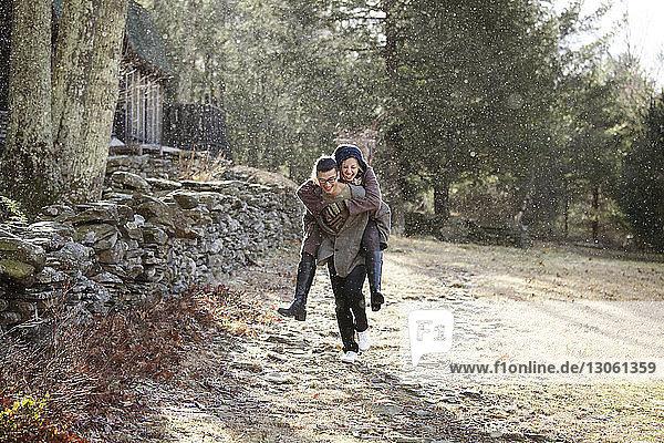 Man piggybacking girlfriend at forest during winter
