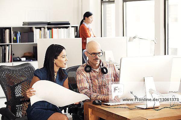 Geschäftsmann und Geschäftsfrau diskutieren  während sie im Büro auf Stühlen sitzen