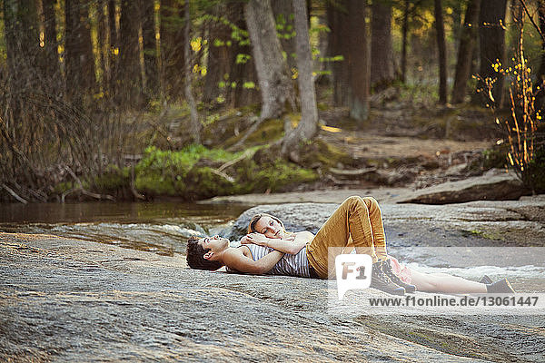 Couple lying on rock at forest