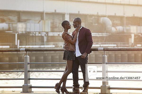 Full length of romantic couple standing by railing against river