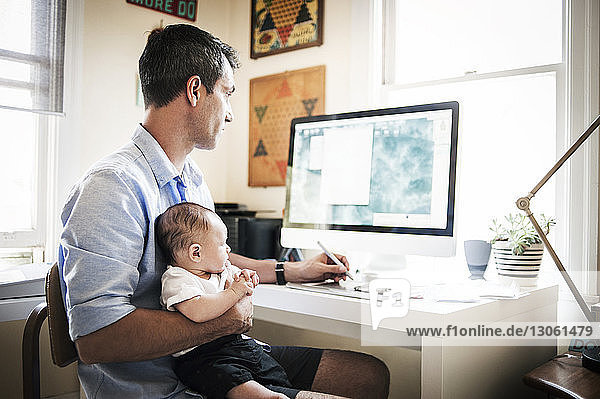Man carrying baby boy while working on desktop computer at home