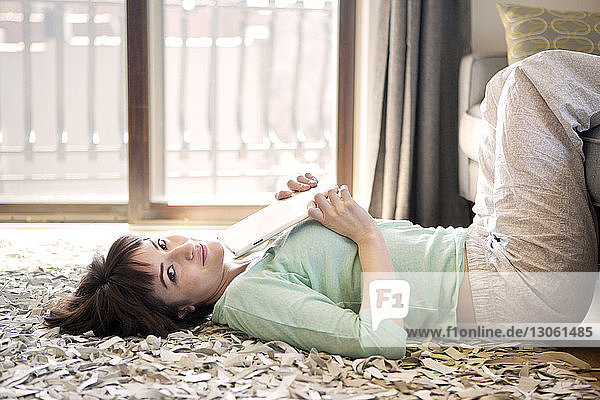 Portrait of smiling woman holding tablet computer while lying on floor at home