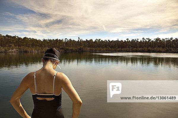 Rear view of woman wearing swimwear standing against lake