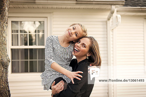 Portrait of mother carrying daughter while standing against house