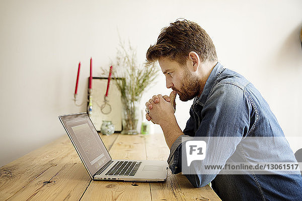 Seitenansicht eines konzentrierten Mannes  der am Tisch sitzend auf den Laptop schaut