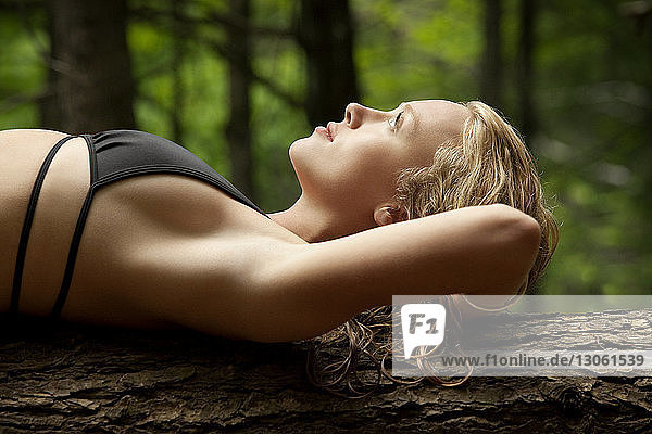 Side view of sensual woman lying on tree trunk