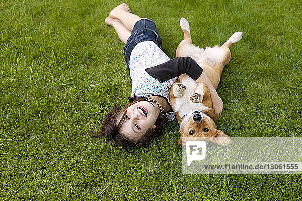 Portrait of girl playing with dog on field in yard